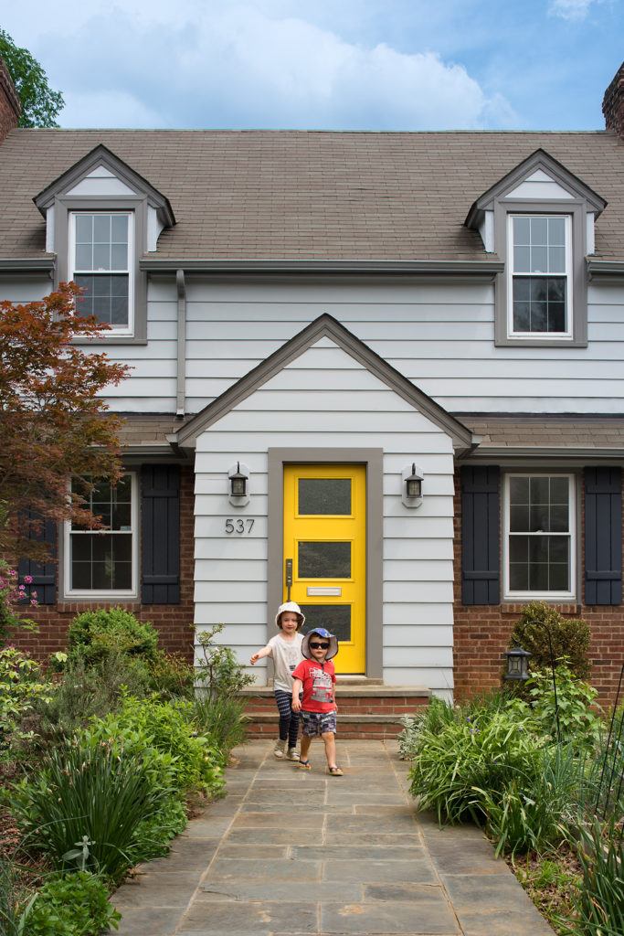 A bright yellow door reflects the homeowners' love of color,